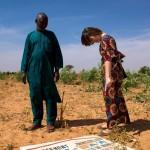 Niamey (Niger), Ceinture Verte. Boubacar Ganda et Ursula Meyer, doctorante à l'Institut de géographie et durabilité. Au sol, le panneau d'un lotissement immobilier, signe du grignotage de cette zone. Photo Maurice Ascani