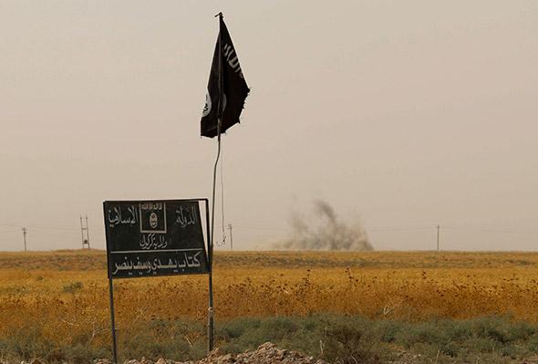 Le drapeau de l'Etat islamique flotte dans la région de Kirkouk, au nord de l'Irak. La fumée au loin provient des combats entre les peshmergas kurdes et les troupes de Daech. © Marwan Ibrahim / AFP / Getty Images
