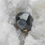Cette binnite (grise) tire son nom du Binntal, en Valais. Nanti d'une pyrite, ce minerai est posé sur des cristaux de dolomite blanche (carbonate de calcium et magnésium). Photos © Stefan Ansermet / Musée cantonal de géologie