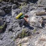 Adrien Pantet tente de localiser et décrire avec précision les contacts entre les différentes roches de la zone (ici entre une dolomie jaune à droite et un calcaire bréchique à gauche). Photo F. Ducrest © UNIL