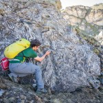 A l'aide d'une boussole, le doctorant mesure l'orientation et l'inclinaison des couches et structures géologiques, dans ce cas très replissées. Photo F. Ducrest © UNIL