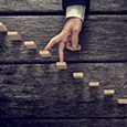 Businessman walking his fingers up wooden steps